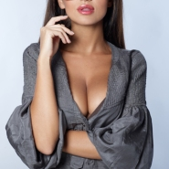 Sexy glamorous woman in a low necked dress showing her cleavage wearing a pair of trendy modern sunglasses looking at the camera with a pout